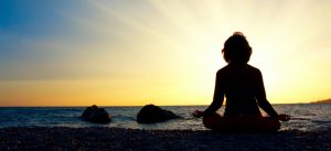woman meditating by the sea